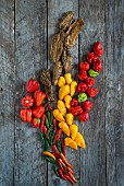 Various chilli peppers on a wooden background