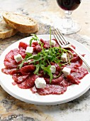 A plate of beef carpaccio with goats cheese