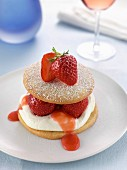 A strawberry sable on a plate in a table setting