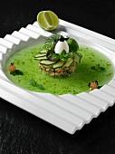 Krabbencocktail dekorativ serviert mit Wachtelei auf grünem Jus
