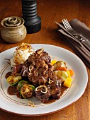 Oxtail casserole with turnips carrots Brussels sprouts caramelized onions mashed potato and gravy