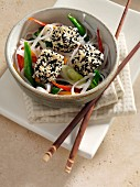 Deep fried tofu coated in black and white sesame seeds rice noodles stir fried vegetables carrots scallions sugar snaps