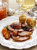Individual portion of leg of pork slices with kumquat marmalade glaze and cheese chive muffins main meals