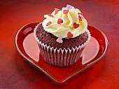 Red Velvet Cupcake auf rotem herzförmigen Teller