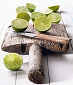 Halved limes on an old wooden board with a knife