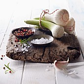 Fresh bulbs of garlic with salt and colourful pepper on a wooden board