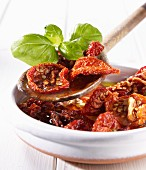 Dried tomatoes in olive oil with basil on a wooden spoon and in a bowl