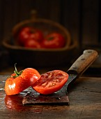 A halved tomato with water droplets on an old butchers knife
