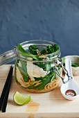 Noodles with chicken, sugar snaps and broccoli in a glass jar (Asia)