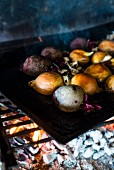 Root vegetables and onions on a charcoal grill