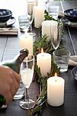 Hand gießt Sekt in ein Glas auf weihnachtlich gedecktem Tisch