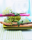 Napkin and chopsticks tied with posy of lady's mantle on green plates