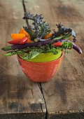 A vegetable bowl containing kale, chillis, pumpkin and long, thin aubergines
