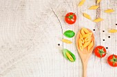 Penne pasta on a wooden spoon with fresh basil and tomatoes