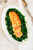 Chicken roulade with ham and spices on sautéed spinach