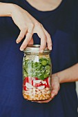 A woman holding a screw-on glass jar of layered vegetable salad