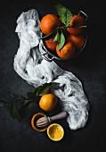 Orangen mit Blättern in Schüssel, weisses Tuch und Zitruspresse