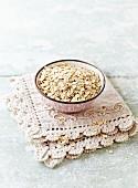 Organic barley flakes in a ceramic bowl