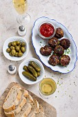 Meatballs with ketchup, olives and cornichons