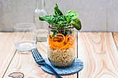 A layered quinoa and carrot salad in a glass