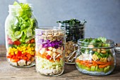 Various layered salads in glass jars