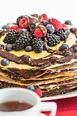 A pancake cake with berries and chocolate sauce
