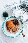 Duck breast with cranberry sauce on a plate in the snow at Christmas