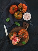 Fresh ripe hairloom tomatoes and basil leaves on rustic wooden board over black stone background