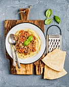 Spaghetti Bolognese with Parmesan cheese, grater and fresh basil