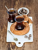 Turkish traditional black tea in a glass and turkish bagel simit on white ceramic serving board