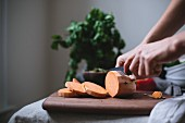 A woman is slicing a sweet potato to use in a sweet potato chili