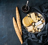 Cheese plate, assortment variety of cheese with walnuts, jam and bread on vintage metal plate