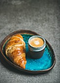 Cup of espresso coffee and croissant in turquoise blue ceramic tray over grey concrete background