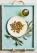Pickled green Mediterranean olives on white ceramic plate, olive tree branch and virgin olive oil in glass bottle