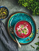 Spring detox beetroot soup with mint, chia, flax and pumpkin seeds on bright blue ceramic plate