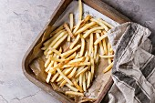 Fast food french fries potatoes with skin served with salt on baking paper in old rusty oven tray
