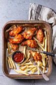 Fast Food: Hähnchenteile mit Pommes Frites und Ketchup auf Ofenblech (Aufsicht)