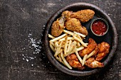 Fast food fried crispy and spicy chicken legs, wings and french fries potatoes with salt and ketchup sauce