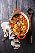 Beef meat stew with potatoes, carrots and spices in cast iron pot on burned black wooden background