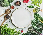 Gemüse, Reis, Hülsenfrüchte und Gewürze kreisförmig um leeren Teller arrangiert
