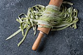Fresh raw uncooked homemade green spinach pasta tagliatelle on wooden rolling pin