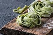 Frische selbstgemachte Spinat-Tagliatelle als Nudelnester auf Holzbrett (Nahaufnahme)