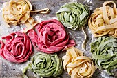 Variety of colored fresh raw uncooked homemade pasta tagliatelle green spinach, pink beetroot and yellow