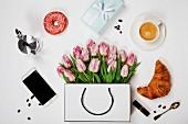 Stillleben mit Tulpen, Kaffee, Handy, Croissant, Donut, Geschenk und Kosmetika (Aufsicht)