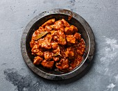 Chicken tikka masala spicy curry meat food in metal plate close-up
