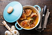 Roast chicken stew in cast iron pan on wooden background