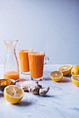 Glasses of orange, lemon and carrot juice with turmeric and ginger
