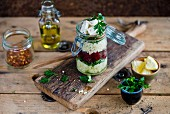 Millet and feta salad with beetroot and parsley in a glass jar