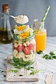 A spoonful of mayonnaise being held over pasta salad with tomatoes, egg and rocket in a glass jar