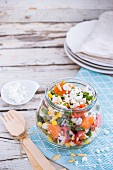 Rice salad with rocket, carrot, sweetcorn, cherry tomatoes and feta in a glass